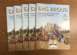 Copies of the printed EMS PROUD fall/winter magazine on a table.